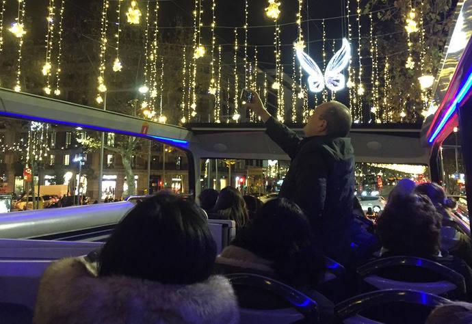 Varios pasajeros disfrutan de la vista de las luces navideñas de Barcelona.