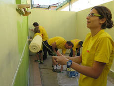 Miembros de DHL pintando instalaciones de la Asociación de Desarrollo e Intervención Abrazo Adi