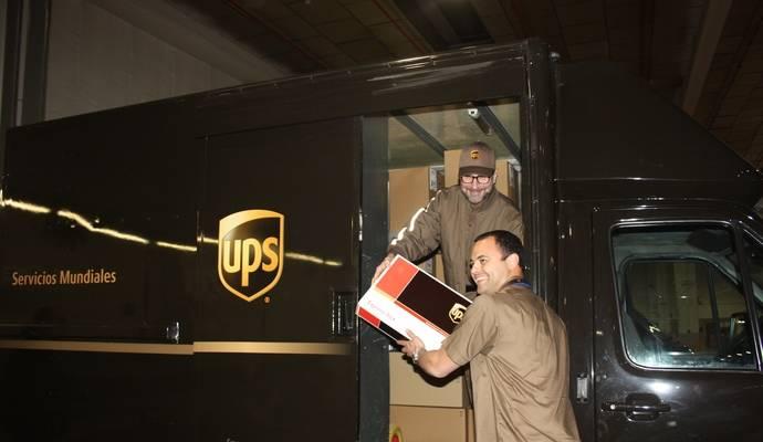 El embajador de EEUU en España, James Costos, recibe un paquete de las manos de Wilfredo Ramos, , director general de UPS España y Portugal.