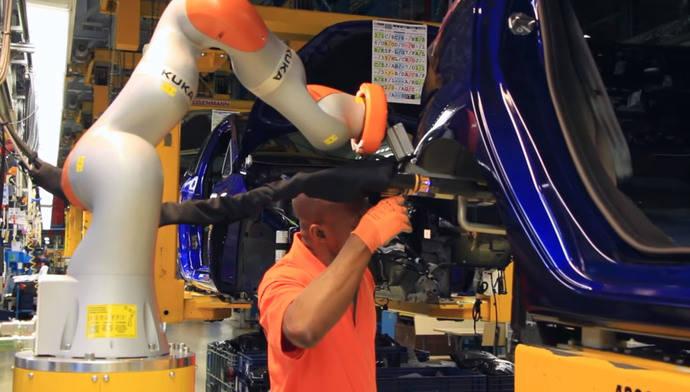 Operarios y robots trabajan juntos en la línea de montaje