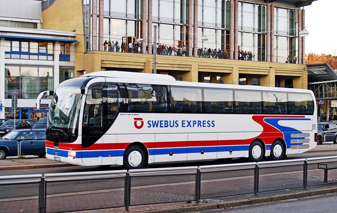 Un autocar circula por una ciudad europea.