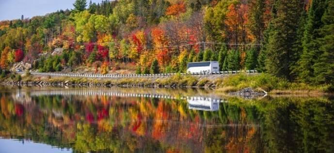 Un autocar circula por una carretera, en el entorno de un lago.