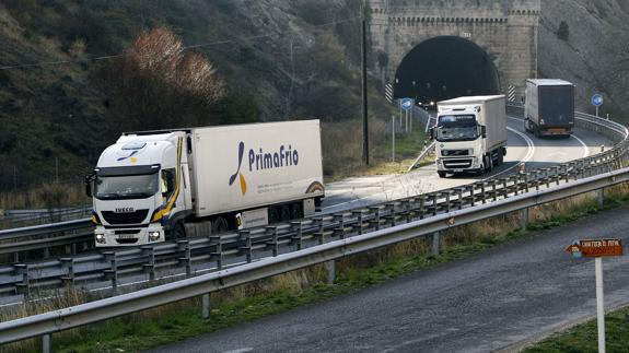 Varios camiones circulan por una carretera.