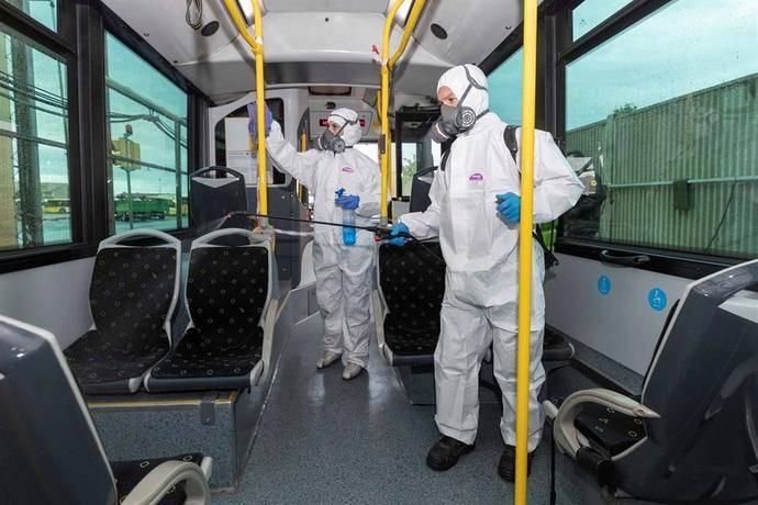Dos trabajadores desinfectan un autobús.