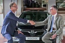 Los responsables de Opel Automobile GmbH y Grupo PSA se estrechan las manos.