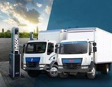 Cargador eléctrico Paccar junto a camiones Kenworth K270E y Peterbilt 220EV.