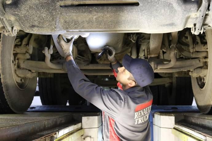 Un mecánico de Renault Trucks trabaja en los bajos de un vehículo.